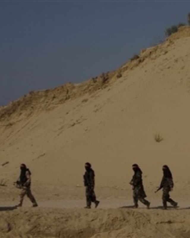 Women soldiers in hijab crossing remote landscape